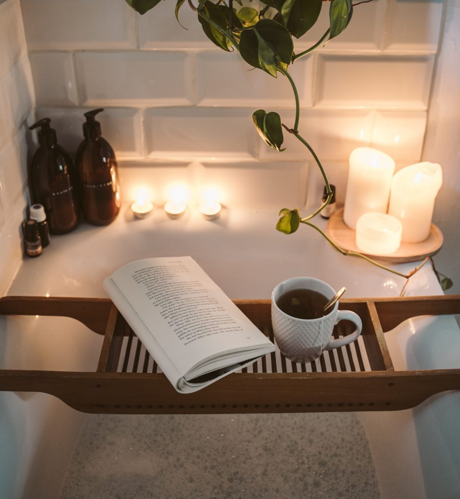 Baño relajante con velas, aceites esenciales aromáticos con una lectura y una taza de té